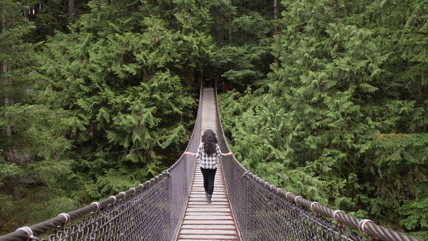 Woman Walking Along Suspension Bridge Alone in Picturesque Green Forest Setting. Lynn Canyon Vancouver, British Columbia, Canada. Surround by Rich Green Trees.