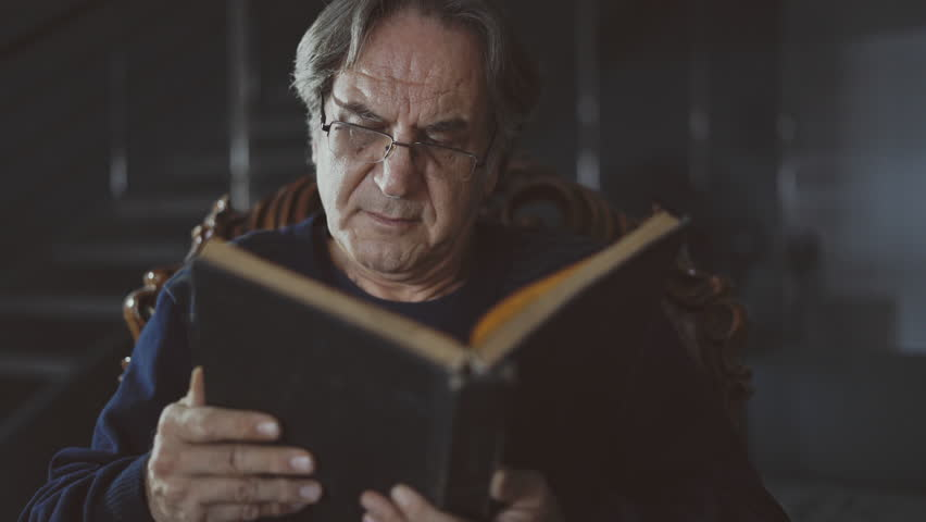 Portrait of an old man reading book