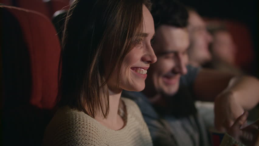 Smiling woman watching movie. Close up of beautiful girl laughing in cinema in slow motion. Boyfriend and girlfriend have fun at movie theater. Romantic date at cinema. Love couple watch comedy film #1015060114