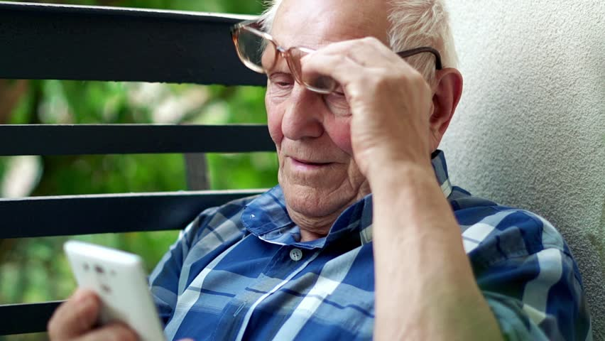 Senior man browsing smarthone on the balcony