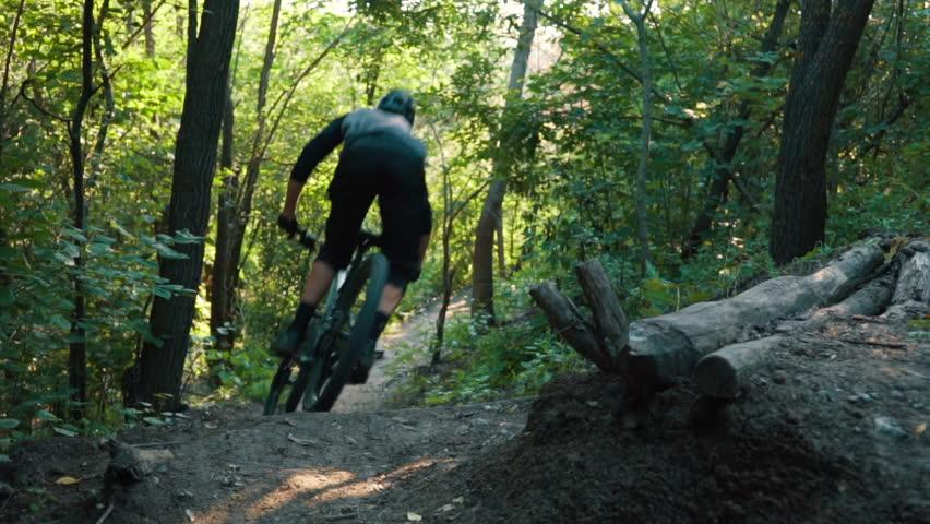 Mountain biker rushes along road in forest, slow motion | Shutterstock HD Video #1015094233
