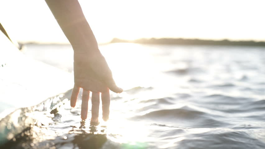 At sunset, close-up the hand of a girl moving through the water | Shutterstock HD Video #1015095145