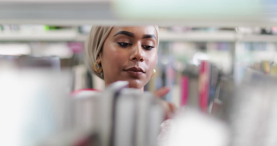 Muslim female student choosing book in library