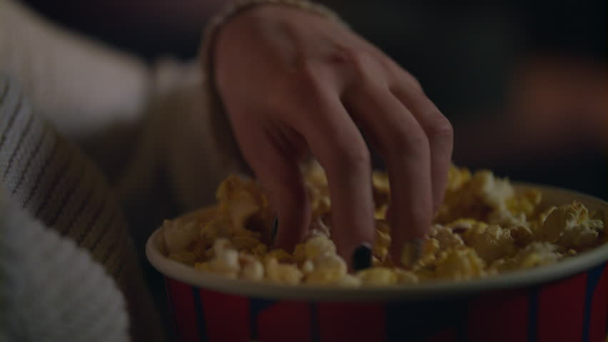 Female hand picking popcorn from paper bucket closeup. Close up of woman eating pop corn at cinema. Movie food concept. Female hand taking popcorn in bucket at cinema | Shutterstock HD Video #1015104943