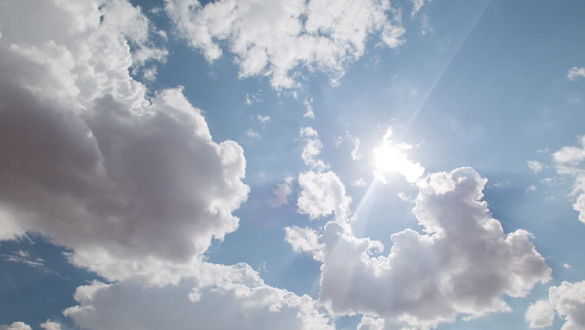 4K time lapse wide shot looking up at the sun shining and casting a lens flare in a blue sky as a fluffy white cloud approaches and obscures it sending light rays and shadows from the cloud