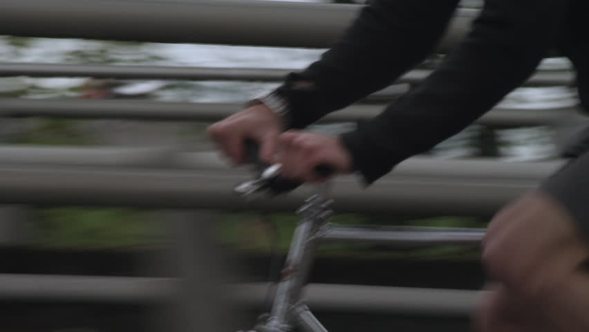 Tilt shot of commuter riding bicycle on bridge in city #1015136503