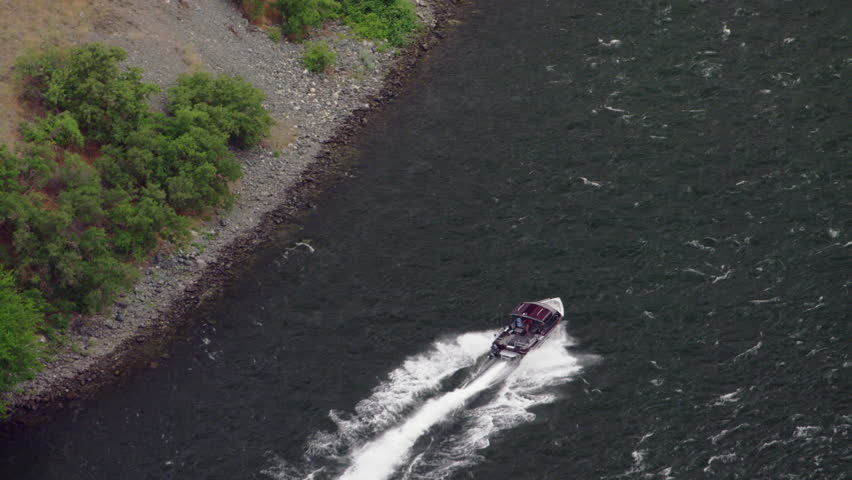 Aerial of a small jet boat cruising up a wide, fast moving river | Shutterstock HD Video #1015145014