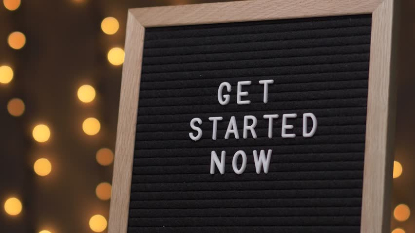 Black letter board with GET STARTED NOW Written on it with white letters. Camera rotating around the sign showing the beautiful bokeh balls in the background. | Shutterstock HD Video #1015157365