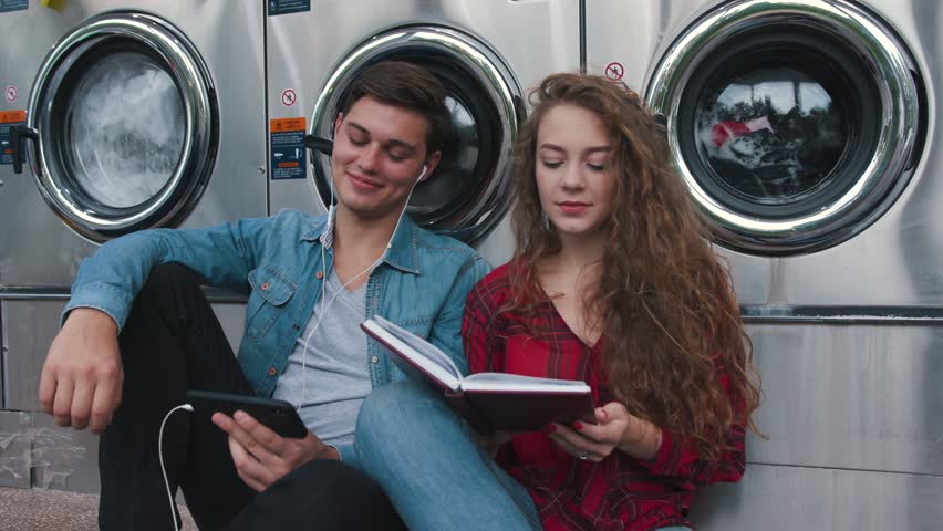 Beautiful couple in a laundry listen to the music on the phone, reading book, watching videos. Handsome young man with stylish hair?ut in jeans shirt. Woman with curly red hair in tartan shirt.
