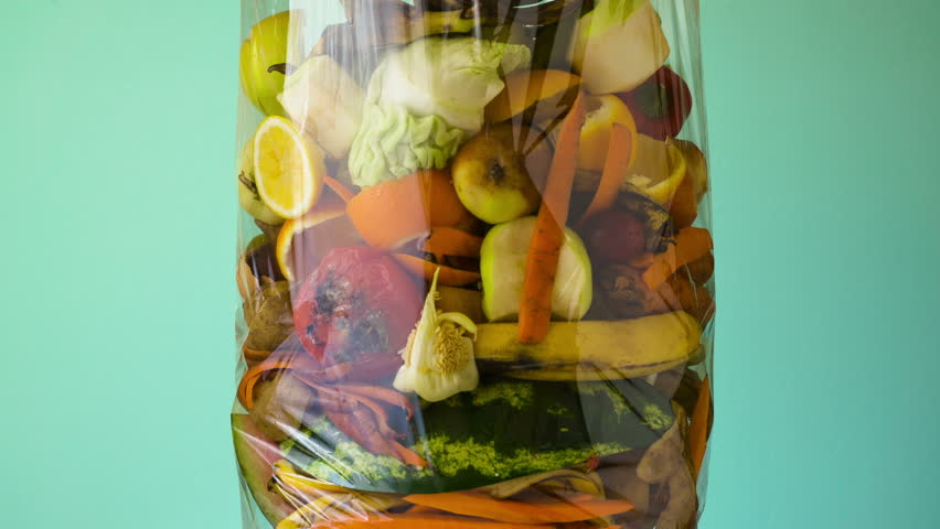 Food waste. Compostable food scraps. Organic kitchen waste for compost with vegetables, fruits and varied food. Filling garbage bag timelapse