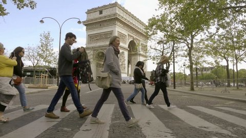 PARIS - MAY 3, 2018: group of people crossing busy street at Arc de Triomphe, happy woman smiling in Paris France Europe. The Arc de Triomphe was designed by Jean Chalgrin in 1806.