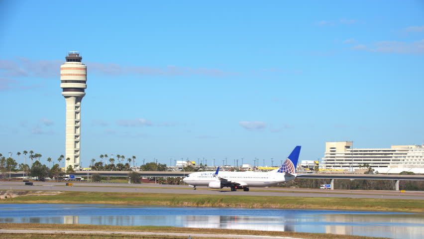 ORLANDO, FL - 2018: United Airlines Boeing 737-800 Jet Airliner Taxiing with MCO McCoy International Airport Landscape in Background on a Sunny Day in Central Florida