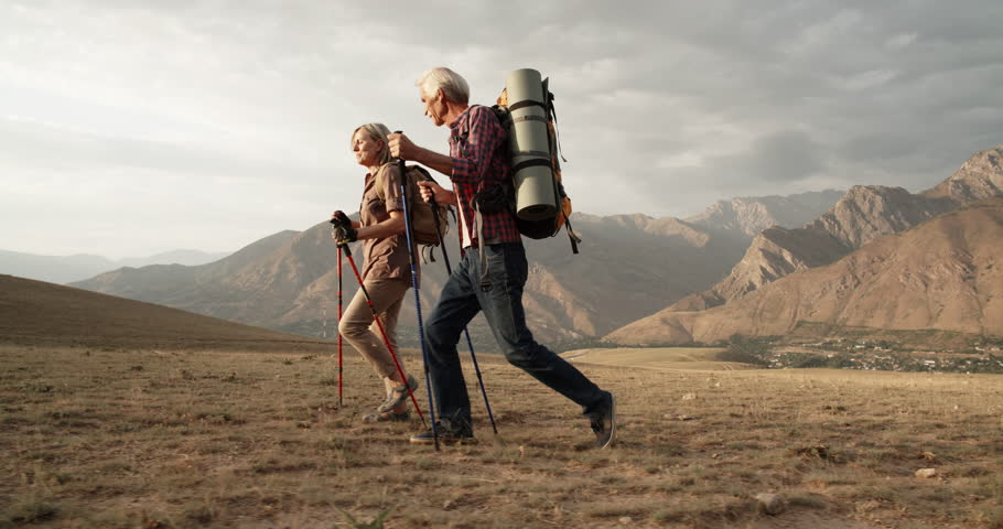 Old caucasian couple hiking, trekking in mountains with backpacks, enjoying their adventure - tourism concept 4k #1015183000