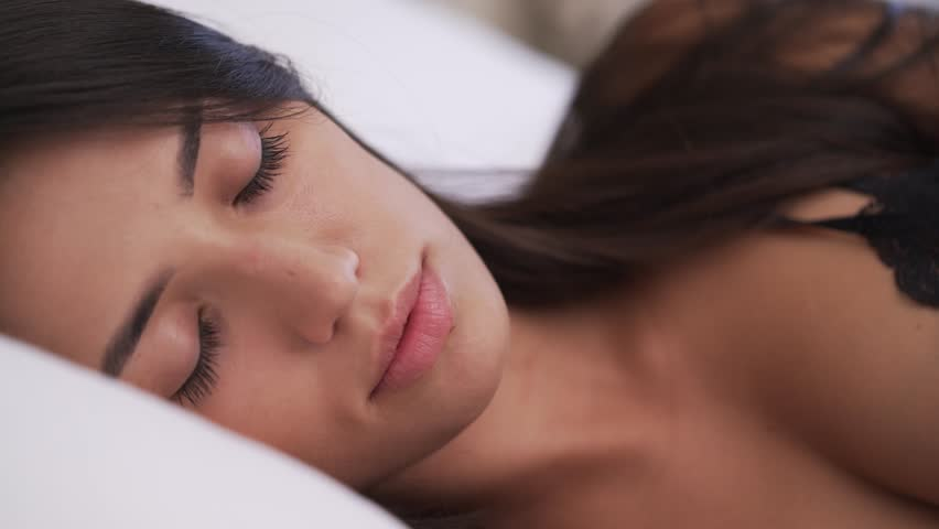 A close-up of a beautiful young woman's face. She is awakening after the sleep. Her hair is on the pillow. Panning camera from the right to the left.
