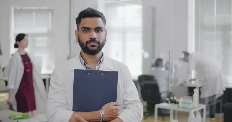 Attractive bearded man in white uniform holding blue folder. Doctor is on background of medical research laboratory with working colleagues | Shutterstock HD Video #1015193479