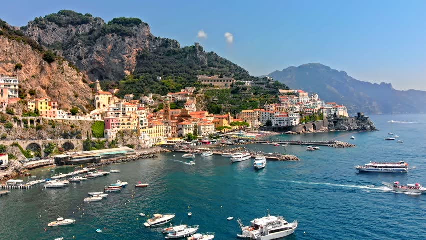 Flying along the old town of Amalfi coast passing a waterway shore port, docks and boats Italy. Aerial drone view