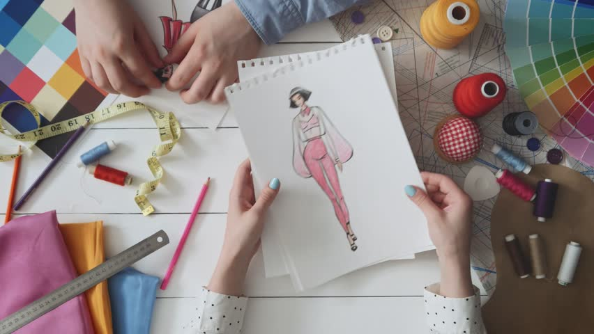 Small team of fashion designers choosing sketches for the new dress | Shutterstock HD Video #1015227034