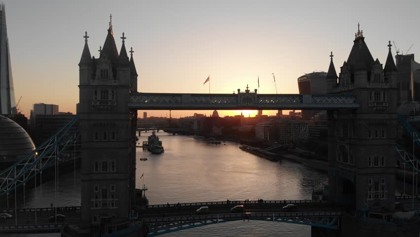 Drone pan towards tower bridge with the sunset and london city in the background.