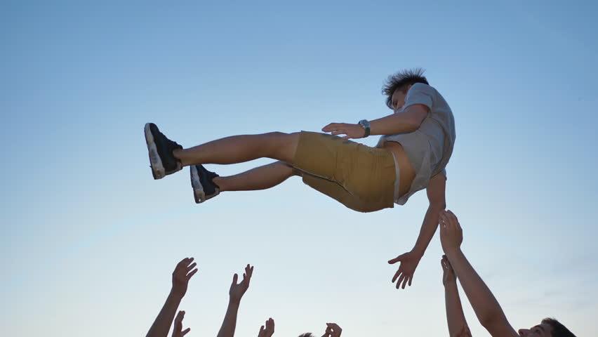 Friends toss their friend on their hands #1015246717
