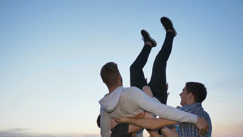 Friends toss their friend on their hands #1015253680