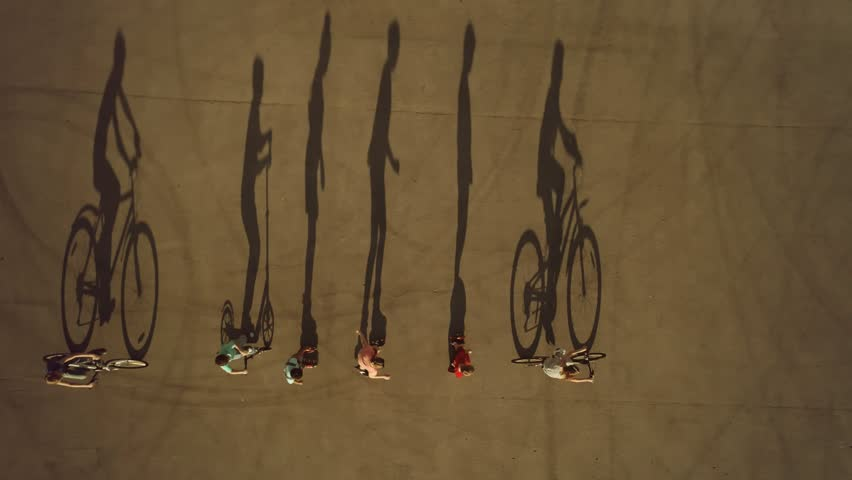 Kids on wheels cast long shadows.Cycling, roller skating and scootering