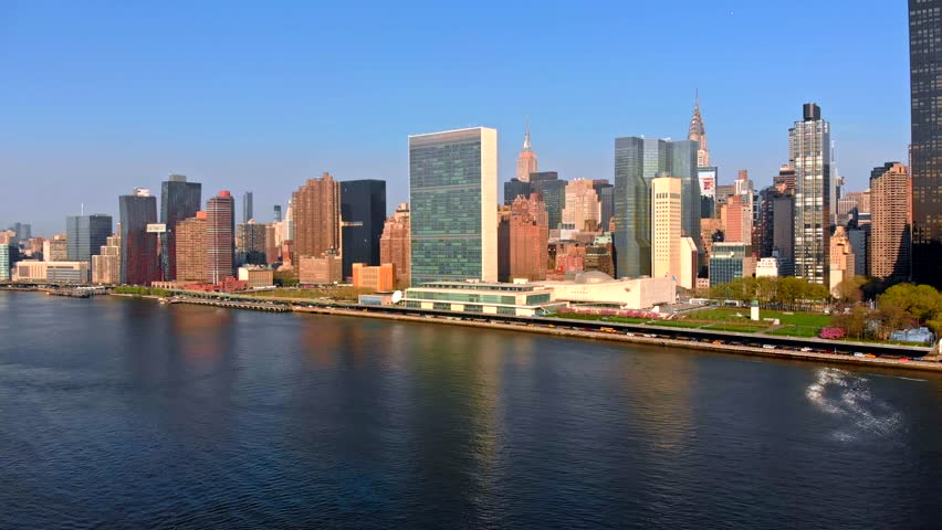 Aerial Drone Footage of New York City flying towards Manhattan skyline over East River viewed from Gantry Plaza State Park in Long Island City Port 4k