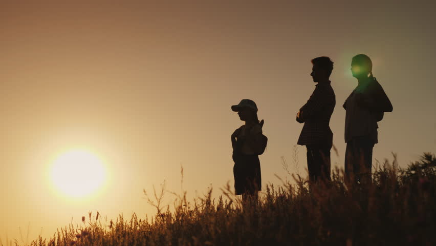 Parents with the child are admiring the sunset. Hike with children concept | Shutterstock HD Video #1015283365