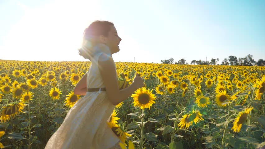 Happy little girl running happy free across the field with sunflowers. slow motion video . smelling big sunflower on summer field. Delight of a pleasant smell. Summer holiday. concept happiness girl
