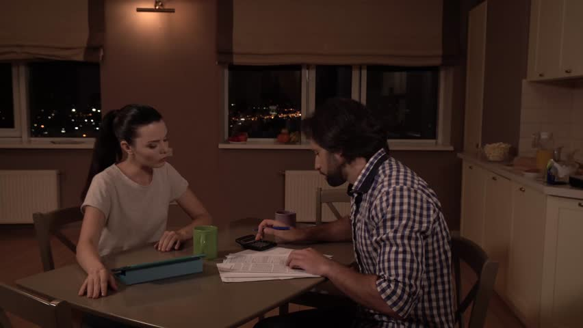 Man and woman sit at table. He count on calculator and wondering. Girl looks at him. She is calm. Girl holds hands near tablet and cup. Man is explaining. He looks at papers. | Shutterstock HD Video #1015291309