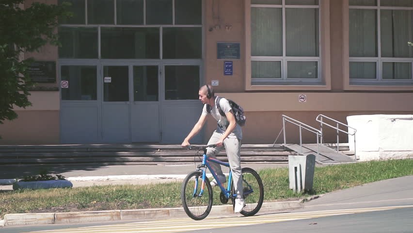 Russia, Samara, August 01, 2018: A young man in headphones riding a bike around the city. Slow motion | Shutterstock HD Video #1015303546