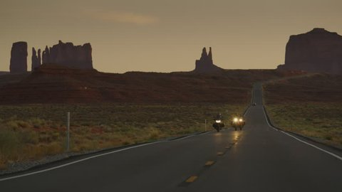 Adventure motorcycles approaching on freeway at dusk / Monument Valley, Utah, United States