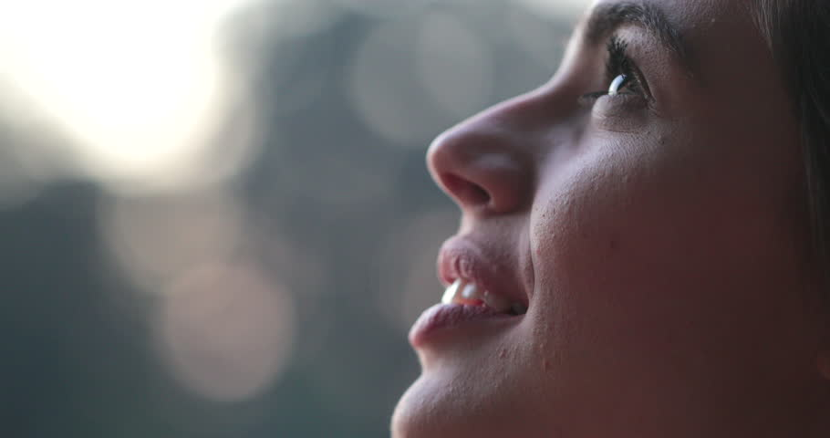 Young woman face opening eyes in meditation and contemplation loooking up at the sky with hope and faith