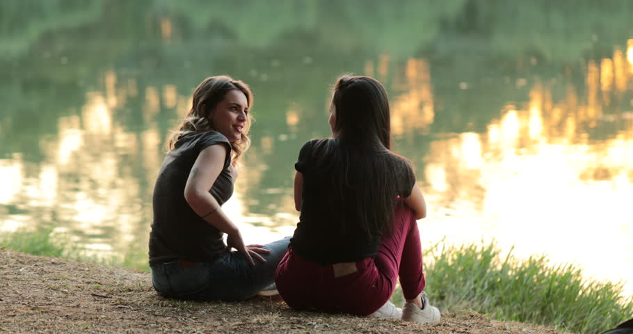 Friends talking by a lake. Girlfriends exchanging ideas and in conversation speaking to one another outdoors in nature #1015310281