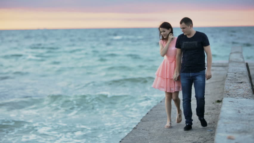 Young man and woman are walking on a stone pier, on the sea. Mainly cloudy. Lovers.