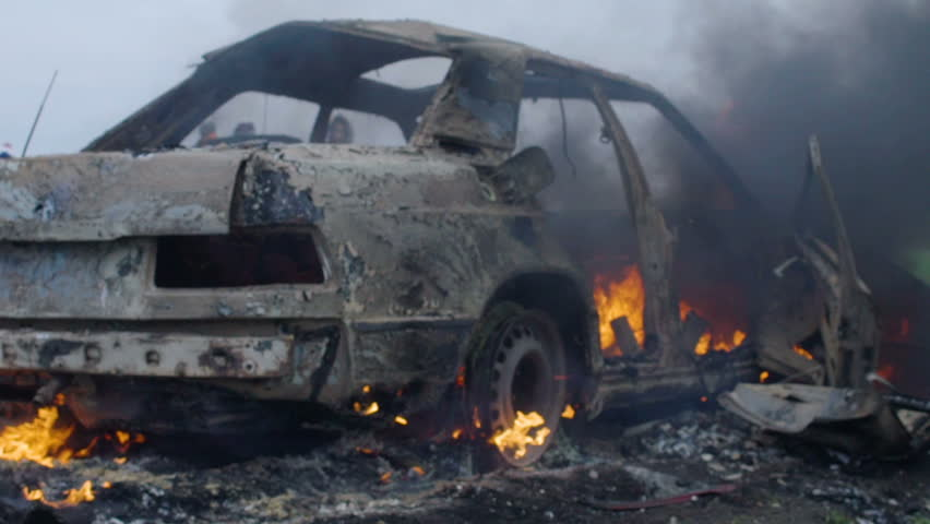 The burning car is in the field, the blown up car is on fire, the car is burning in slow motion