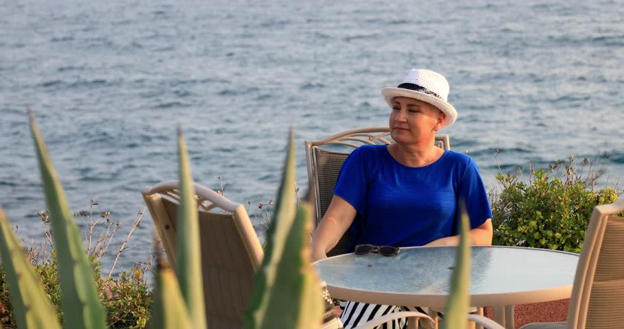 Portrait of a positive female cancer patient sitting and relaxing near the sea