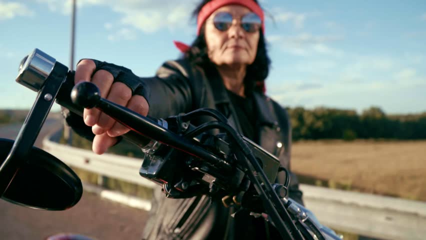 The old biker sits at the wheel of his motorcycle. On a steep motorcycle sits an elderly woman in round glasses, she has a red bandana and a leather jacket, and gloves. An old biker with a nature