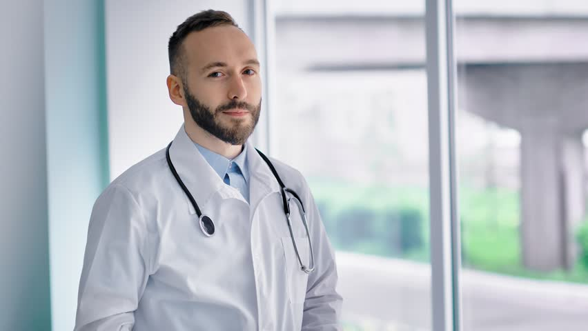 Confident Caucasian male doctor in white lab coat looking into camera | Shutterstock HD Video #1015312534