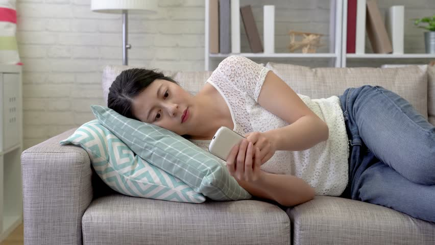 Sleepy Asian woman lying on the sofa just received some rude and annoying advertisement message. She was in a rage and threw her phone away. | Shutterstock HD Video #1015316170