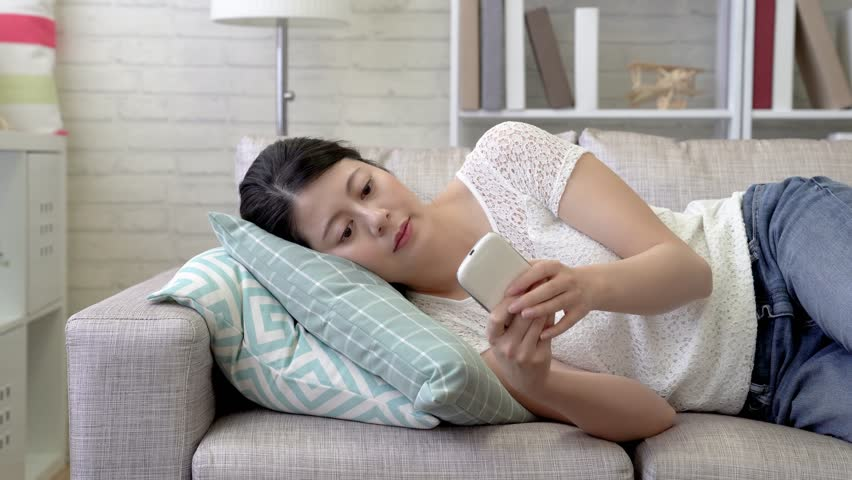 Boring woman lying on the couch tapping on her cell phone. Sudden she received some annoying message from others and burst into rages and threw away her cell phone. | Shutterstock HD Video #1015316455