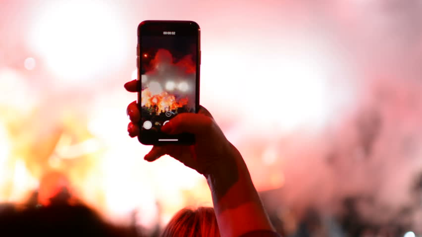 Taking a photo with mobile phone iPhone during rock band music performance concert on stage Royalty-Free Stock Footage #1015324228