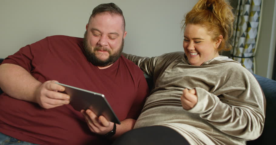 4K Overweight couch potato couple laughing hard at funny internet content on computer. Slow motion.