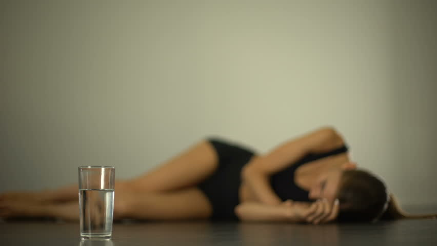 Anorexic girl lying on floor, suffering from stomach pain, nausea, bulimia