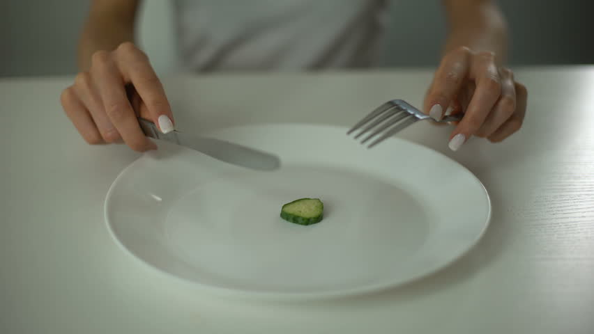 Girl slicing cucumber, obsessed with undereating, fear of overweight, anorexia
