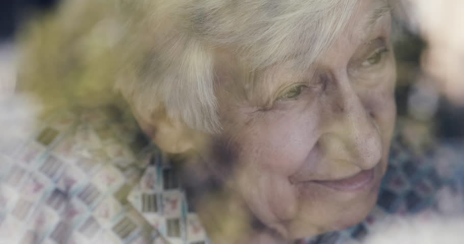 An old lady looks out the window and smiles. In the window you can see the reflections of the nature that surrounds it outside the house. Concept of: life, drought, elderly support and nursing home.