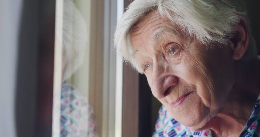 An old woman looks out the window and smiles. In the window. Concept of: life, drought, elderly support and nursing home and happiness.
