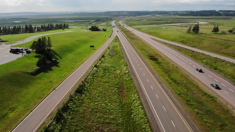 An aerial shot of cars driving on a highway going through lush green fields