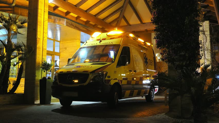 Ambulance with Flashing Siren Lights Parked By Emergency Department