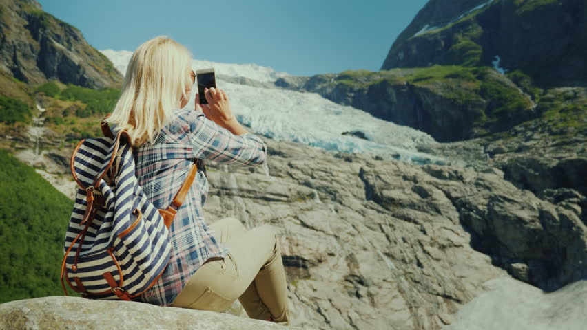 Woman tourist taking pictures of the glacier. Traveling in Norway concept | Shutterstock HD Video #1015365475