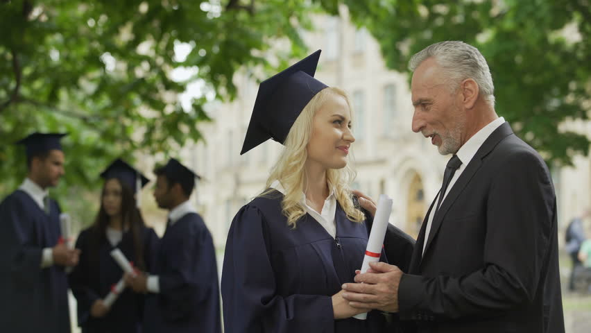 Happy father congratulating graduate daughter and kissing her near university #1015380421